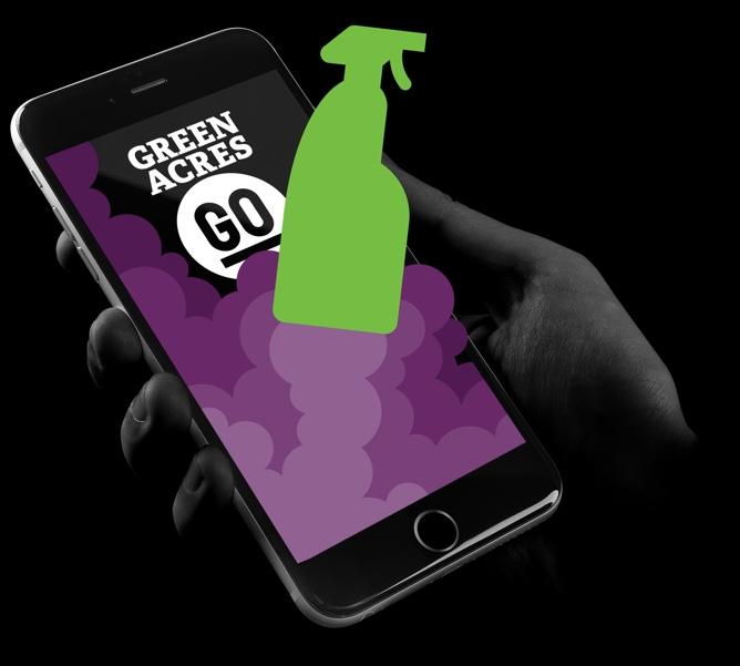 A persons hand holding an iphone with the Green Acres Go app open. An image of a bottle of cleaning product is blasting off like a rocket is visible on the phone.